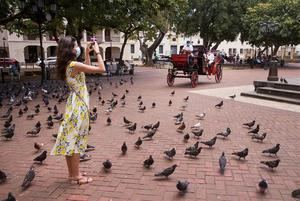 Una turista toma fotografías en el parque Colón mientras que coches impulsados con energía eléctrica circulan por la zona colonial hoy en Santo Domingo, República Dominicana.
