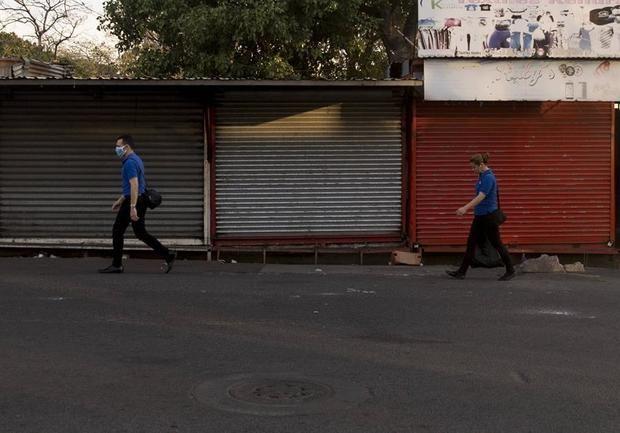Dos personas caminan frente a varias tiendas cerradas en Managua, Nicaragua.