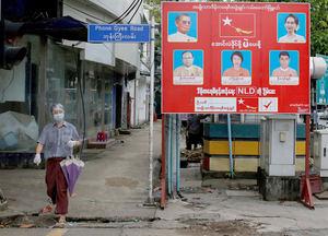 Un hombre con mascarilla se acerca a un letrero de campaña electoral del partido de la Liga Nacional para la Democracia (LND), dirigido por la Consejera del Estado de Myanmar, Aung San Suu Kyi, en Yangon, Birmania, elecciones que ganó el 8 de noviembre de 2020.