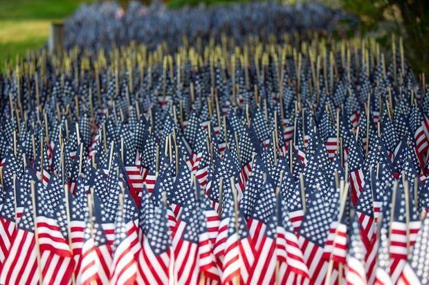 Más de 8.000 banderas, situadas en el patio de Mike Labbe en Grafton, rinden homenaje a las muertes de Covid -19 en Massachusetts, EE.UU.