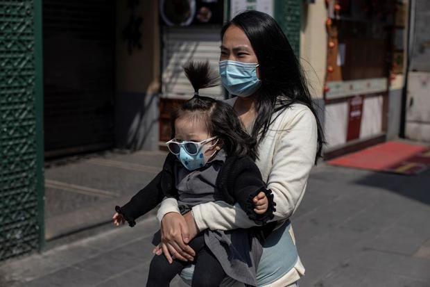 Una mujer y un bebé, con mascarillas, pasean por la calle comercial Qianmen de Pekín (China) este viernes, en medio de la pandemia por coronavirus.