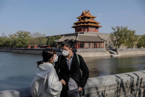 Una pareja con mascarillas visitan una zona próxima a la Ciudad Prohibida en Pekín, China.