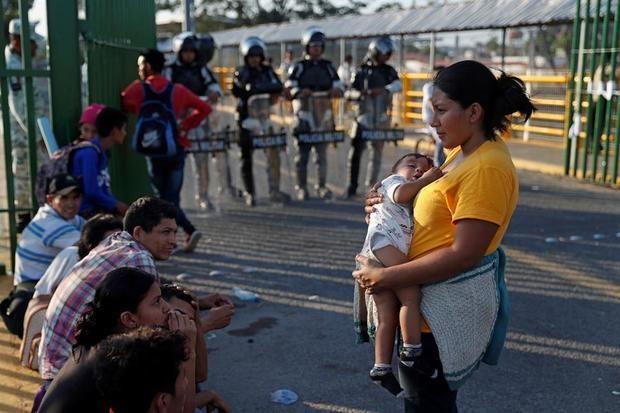 Policía mexicana resguarda la entrada del frontera hacia México en el puente Rodolfo Robles que divide el país con Guatemala, para evitar que migrantes hondureños, de la nueva caravana de migrantes, ingrese sin pasar el registro exigido por el Gobierno, este sábado, en Tecún Umán, Guatemala.