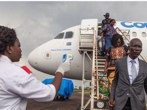 Una funcionaria de salud usa un termómetro para evaluar a los pasajeros que llegan al aeropuerto de Mbandaka, en la República Democrática de Congo.