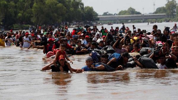 La caravana de migrantes cruza a pie el río que separa a Guatemala de México