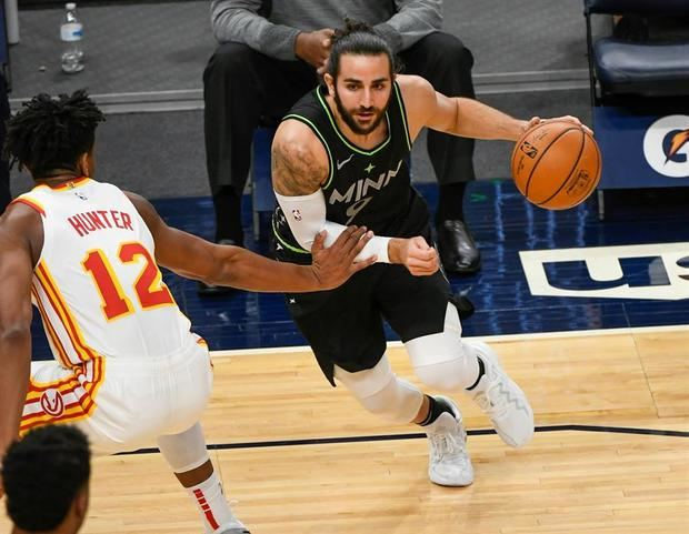 El español de Timberwolves Ricky Rubio (d) avanza con el balón frente a De'Andre Hunter de Atlanta Hawks.