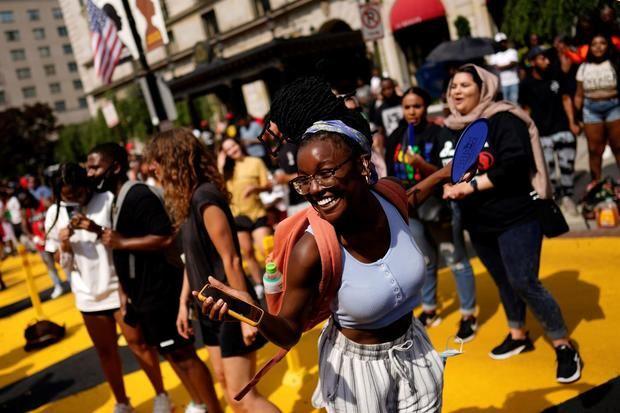 Personas celebran el 'Juneteenth', fecha que conmemora el fin de la esclavitud de la comunidad afroamericana, este 19 de junio de 2021, en la Black Lives Matter Plaza, de Washington.