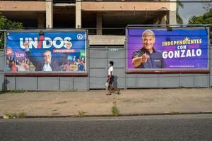 Hombres con tapabocas son vistos mientras pasan cerca a una valla publicitaria del candidato presidencial Luis Abinader, este sábado en Santo Domingo (República Dominicana).