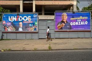 Una mujer con tapabocas es vista mientras camina cerca a vallas publicitarias de los candidatos presidenciales Luis Abinader y Gonzalo Castillo, este sábado en Santo Domingo.