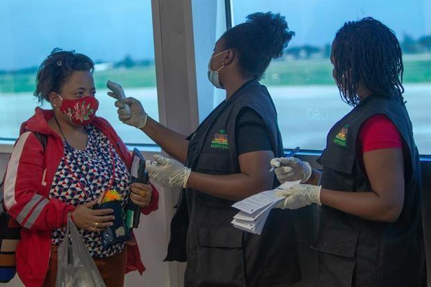 Trabajadores del aeropuerto toman la temperatura y el registro a los pasajeros que llegan el 1 de julio de 2020, al Aeropuerto Internacional Toussaint Louverture de Puerto Príncipe (Haití).