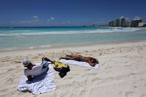 Vista de dos turistas tomando el sol en una playa de Cancún, en el estado de Quintana Roo (México). El Caribe mexicano, con su reconocida zona hotelera de Cancún, se resiente ante el impacto por la pandemia de coronavirus y registró este lunes un 36 % de ocupación, señalaron las autoridades.