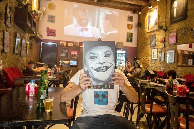 Un hombre sostiene el menú con la foto del personaje Joker en el bar Cine Botequin, el 5 de octubre de 2021, en Río de Janeiro, Brasil.