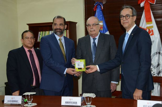El embajador dominicano en España, Olivo Rodríguez Huerta, al director del Archivo General dominicano, Roberto Cassá, en presencia del señor José Màrmol y un funcionario del AGN.