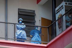 Dos trabajadores de la salud permanecen en un balcón del Hospital Universitario de Caracas, en Caracas, Venezuela.