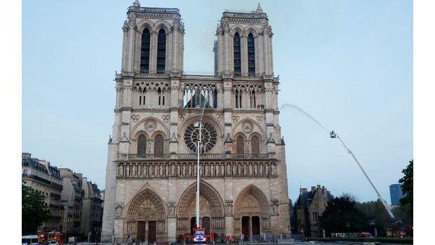 Los miembros de la brigada de bomberos de París rocían agua sobre la fachada de la catedral de Notre Dame este lunes, en Paris (Francia).