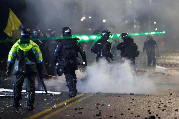 Integrantes del Escuadrón Móvil Antidisturbios (ESMAD) se enfrentan a manifestantes durante una jornada de protestas en Bogotá, Colombia.