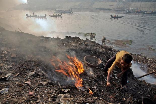 Fotografía cedida por el Fondo de las Naciones Unidas para la Infancia (Unicef) donde aparece un niño quemando basura mientras está parado sobre un montón de escombros a orillas del río Buriganga, en Hazaribagh, un subdistrito del distrito central de Dhaka, Bangladés.