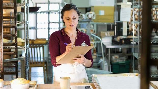 Fotografía promocional cedida por Mastercard que muestra a una mujer mientras posa en panadería comercial.