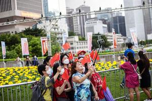 Un grupo de mujeres se toman fotografías mientras sujetan banderas chinas en Hong Kong, China. Un grupo de mujeres se toman fotografías mientras sujetan banderas chinas en Hong Kong, China.