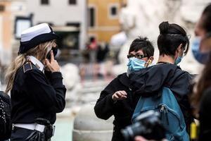 Un policía italiano vigila que los visitantes de la Fontana de Trevi, en Roma, llevan mascarilla.