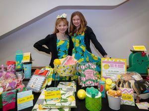 """Hailey Hertzman (izda.) y Katie Vonder Haar muestran algunos de los productos en venta de su negocio """"Ooh La Lemon"""". (© Lemonade Day)"""