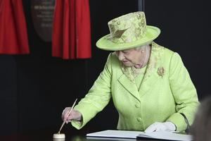 La reina Isabel II de Inglaterra firmaba en el libro de visitantes a su salida de la exposición del Titanic en Belfast, Irlanda del Norte, durante una visita a laregión británca en 2012.