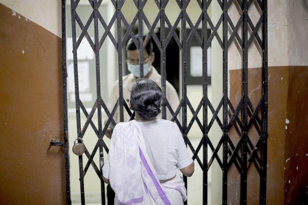 Una mujer espera para ser vacunada en un centro de Calcuta.