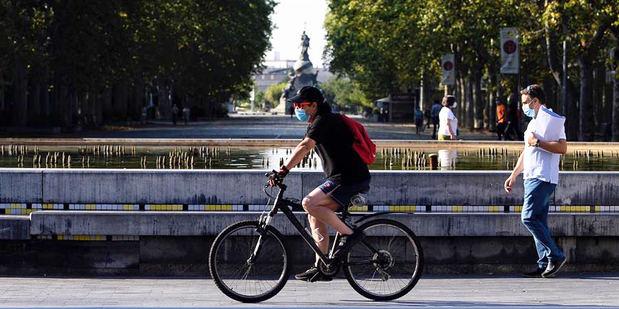 Un hombre circula en bicicleta y con mascarilla por el centro de la ciudad de Valladolid (España) donde este viernes las temperaturas superarán los 35 grados centígrados.