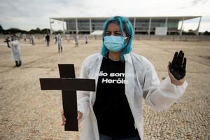 Una enfermera fue registrada este sábado al sostener una cruz, durante una protesta simbólica en honor a los profesionales de la salud y por las más de 400.000 muertes por el nuevo coronavirus en Brasil, frente al Palacio do Planalto, en Brasilia (Brasil).