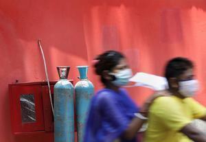 Una familia de un paciente con covid-19 pasa cerca de algunos cilindros de oxígeno en un hospital en Kolkata, India Oriental, el 28 de abril de 2021.