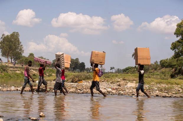 Varios inmigrantes irregulares haitianos cruzan el río Masacre, frontera natural entre Haití y República Dominicana.