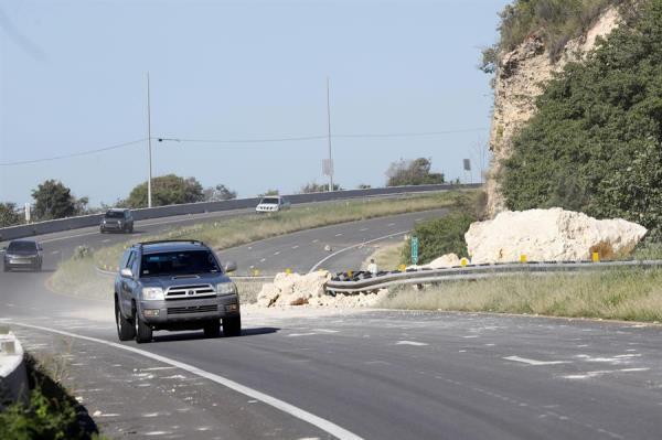 Vehículos pasan junto a las piedras que bloquean una de las calzadas de una carretera afectada tras el sismo registrado este martes, en la entrada de la ciudad de Ponce (Puerto Rico).