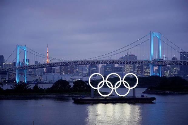Los aros olímpicos iluminan el agua cerca del Puente del Arco Iris en el Parque Marino de Odiaba, Japón.