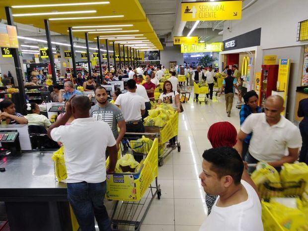 Personas esperando en fila en supermercado.
