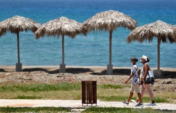 Dos personas con tapabocas caminan frente al mar , en La Habana, Cuba.