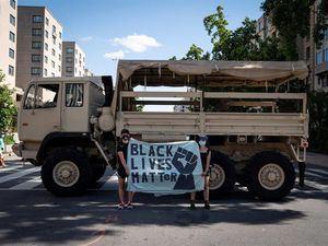 Dos personas protestan en un camión de la Guardia Nacional cerca de la Casa Blanca, donde ha habido una semana de protestas por la muerte de George Floyd, quien murió bajo custodia policial, en Washington, DC.