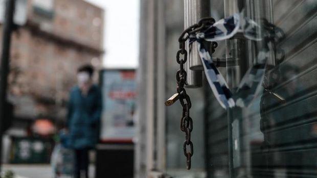 Las cadenas de un comercio cerrado fueron registradas este miércoles, con la silueta de una persoana con tapabocas al fondo, en la capital argentina.