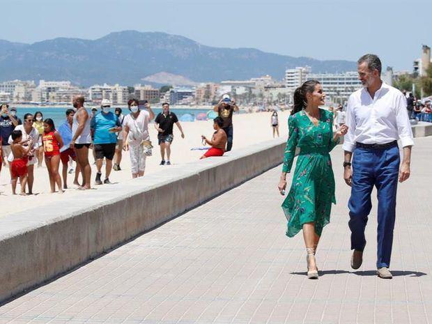 Los reyes pasean por la playa de Palma, inusualmente despoblada por la crisis