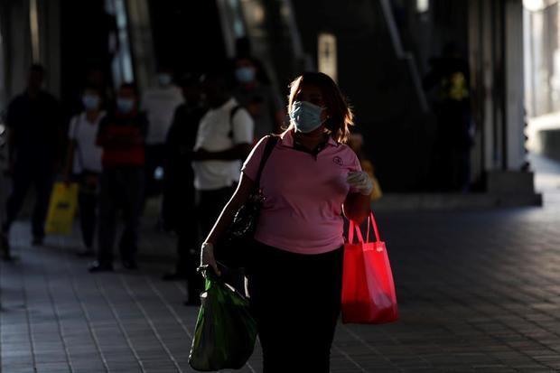Una mujer usando un tapabocas camina, este lunes, por las calles en Ciudad de Panamá, Panamá.