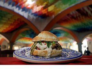 Fotografía de una hamburguesa que lleva los ingredientes del tradicional chile en nogada, en un restaurante de Puebla, México.