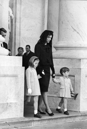 Jacky Kennedy junto a dos de sus hijos saliendo del funeral del presidente Kennedy.