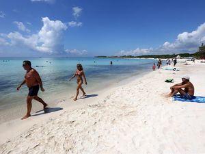 Turistas disfrutan del clima en Playa Punta Esmeralda, hoy jueves en el municipio de Solidaridad, Quintana Roo, México.