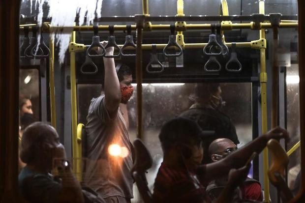 Personas con tapabocas son vistas en un autobús en la ciudad de Río de Janeiro, Brasil.