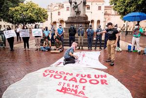Un grupo de personas protesta junto a una estatua de Cristóbal Colón hoy, día en el que se conmemora el 529 aniversario de la llegada del almirante a América, en Santo Domingo, República Dominicana.