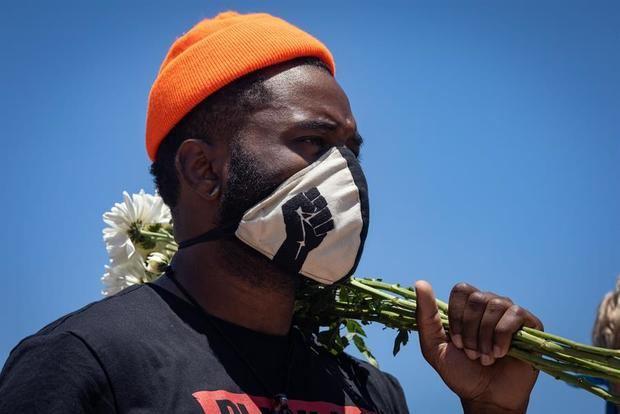 Un hombre sostiene un ramo de flores durante una protesta de 'Black Lives Matter' (Las vidas negras importan), en las afueras de la Universidad del Sur de California en Los Ángeles, EE.UU.
