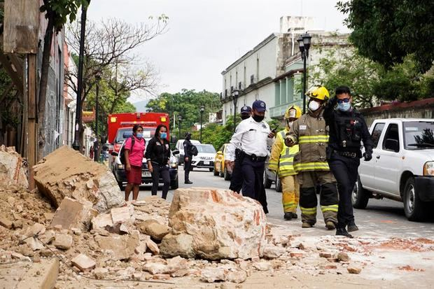 Miembros de la policía y de los bomberos observan los daños causados en una barda derrumbada este martes, en la ciudad de Oaxaca, México.