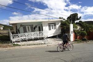 Una persona en bicicleta pasa delante de una casa dañada por el temblor de magnitud 5,8 que se reportó este lunes a las 06.32 hora local (10.32 GMT) en la costa de Guánica, municipio del suroeste de Puerto Rico.