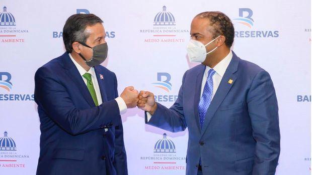El ministro de Medio Ambiente, Orlando Jorge Mera; y el administrador general de Banreservas, Samuel Pereyra, se saludan luego de firmar un acuerdo para la preservación del manatíes antillanos.