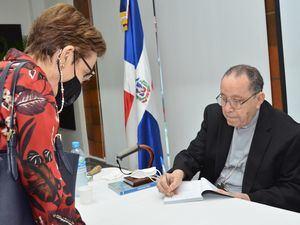 Monseñor Príamo Tejeda firma un ejemplar a Carmen de Armenteros.