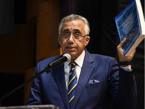 """Luis Mejía Oviedo, presidente del COD, sostiene un ejemplar del libro """"El Deporte Dominicano y su Entorno"""" Parte II."""